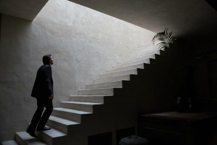 Photo du film Knight of Cups de Terrence Malick. Dans une pièce sombre, Christian Bale se tient en bas d'un escalier et regarde vers le haut d'où provient la lumière. Il semble gravir les marches de l'escalier.