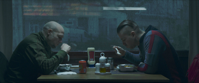 Photo de Jeroen Perceval et Kevin Janssens dans le film Les Ardennes de Robin Pront. Nous voyons les deux frères en train de manger face à face dans un restaurant, pris de profil.