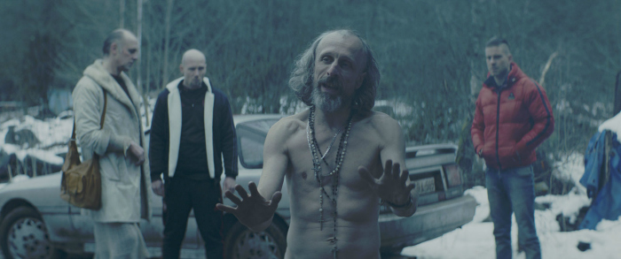 Photo de Jan Bijvoet, Jeroen Perceval et Kevin Janssens dans le film Les Ardennes de Robin Pront. Un personnage torse nu est au premier plan et semble argumenter face à un autre protagoniste. Au second plan, d'autres personnages se tiennent autour d'une voiture et semblent particulièrement sur leurs gardes.