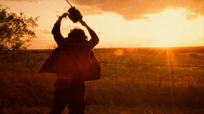 Photographie de Gunnar Hansen dans le film Massacre à la tronçonneuse de Tobe Hooper. Leatherface lève sa tronçonneuse en l'air et semble gesticuler dans tous les sens, fou de rage.