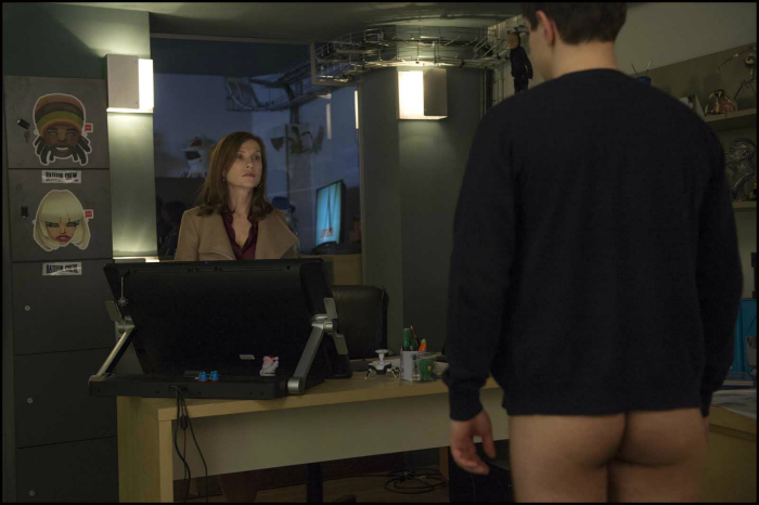 Photo du film Elle de Paul Verhoeven. Dans un bureau, Isabelle Huppert contemple un homme de l'autre côté d'un poste de travail qui a le pantalon baissé.