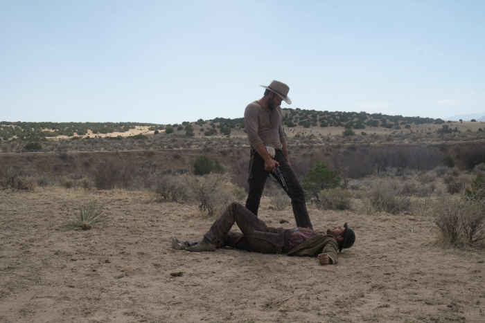Photo de Joel Edgerton dans le film Jane Got a Gun. L'acteur pointe son arme sur un homme couché dans le désert qu'il vient de maîtriser.