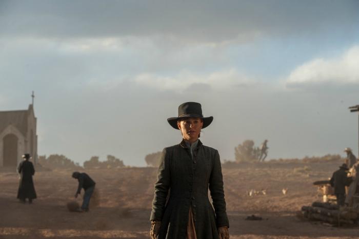 Photo de Natalie Portman dans le film Jane Got A Gun. L'héroïne rentre dans la rue principale d'une ville qui ne semble pas très animée.