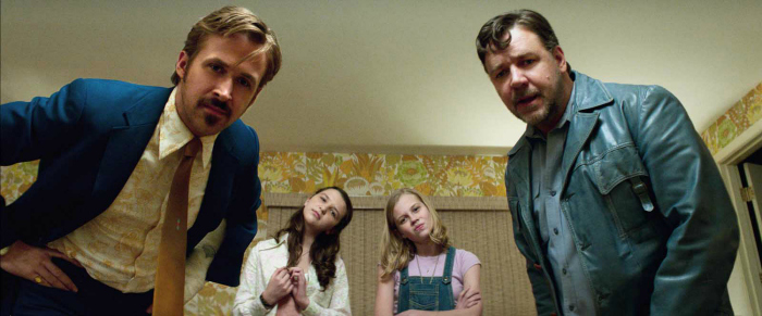 Photo de The Nice Guys de Shane Black. Nous y voyons au premier plan Russel Crowe et Ryan Gosling face à l'objectif en train de regarder un autre personnage avec un air perplexe. Au second plan, deux jeunes filles contemplent ce même personnage.
