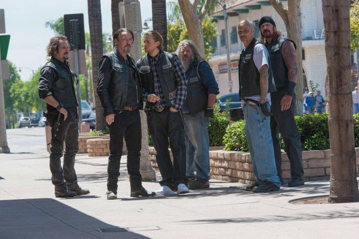 Photo de la saison 7 de Sons of Anarchy. Nous y voyons les principaux membres du SAMCRO dans une rue de Charming. De gauche à droite : Tig, Chibs, Jax, Bobby, Happy, Quinn.