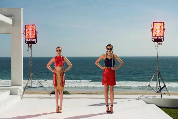 Photo d'Abbey Lee et Bella Heathcote dans le film The Neon Demon de Nicolas Winding Refn. Les deux mannequins posent face à l'objectif devant une plage et font des pauses identiques.