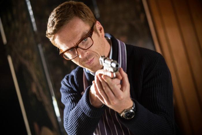 Photo de Damian Lewis dans le film Un traître idéal. Face à l'objectif, le comédien tient une arme déchargée et semble l'analyser minutieusement.