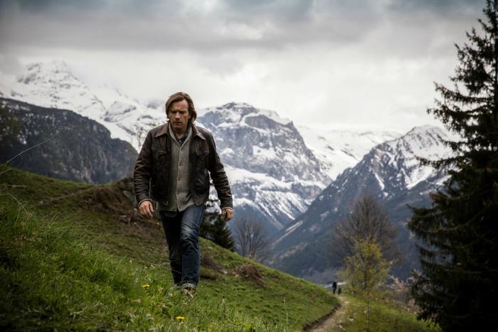 Photo d'Ewan McGregor dans le film Un traître idéal qui marche dans les Alpes françaises face à l'objectif.