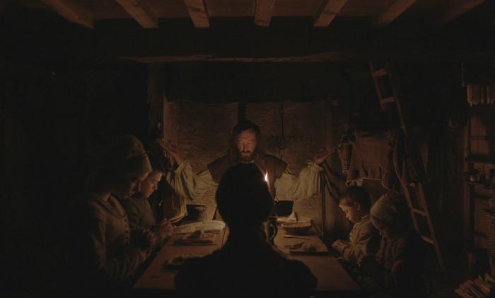 Photo du film The Witch dans laquelle nous voyons une famille manger autour d'une table dans une pièce très sombre éclairée par des bougies.