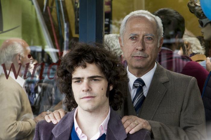 Photo de Guillermo Francella et Peter Lanzani dans le film El Clan. Posant pour une photo, le père Puccio met les mains sur les épaules de son fils.