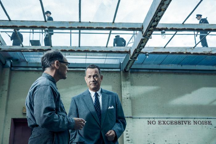 Photo de Mark Rylance et Tom Hanks dans le film Le Pont des Espions de Steven Spielberg. Les deux hommes discutent dans une cour de prison recouverte par des grillages. Des policiers sont en haut de la cour.