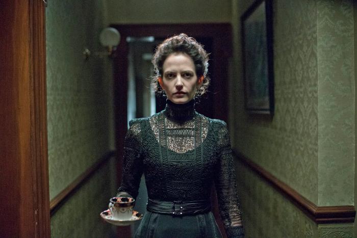 Photo d'Eva Green dans la première saison de Penny Dreadful qui avance face à l'objectif dans un couloir sombre d'un immeuble victorien, une tasse de thé à la main.