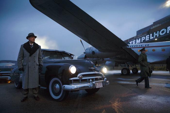 Photo de Tom Hanks sur un aéroport dans le film Le Pont des Espions de Steven Spielberg. Dans un décor des années 50, Hanks sort d'une voiture et s'apprête à monter dans un avion.