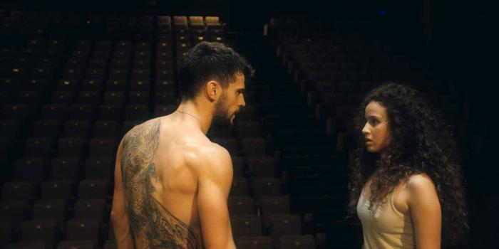 Photo de Kevin Mischel et Oulaya Amamra dans le film Divines, s'apprêtant à danser ensemble sur la scène d'une salle vide.