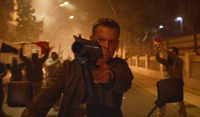 Photo de Matt Damon dans le film Jason Bourne de Paul Greengrass. L'acteur tient une arme automatique et vise alors qu'il est à moto dans les rues d'Athènes.