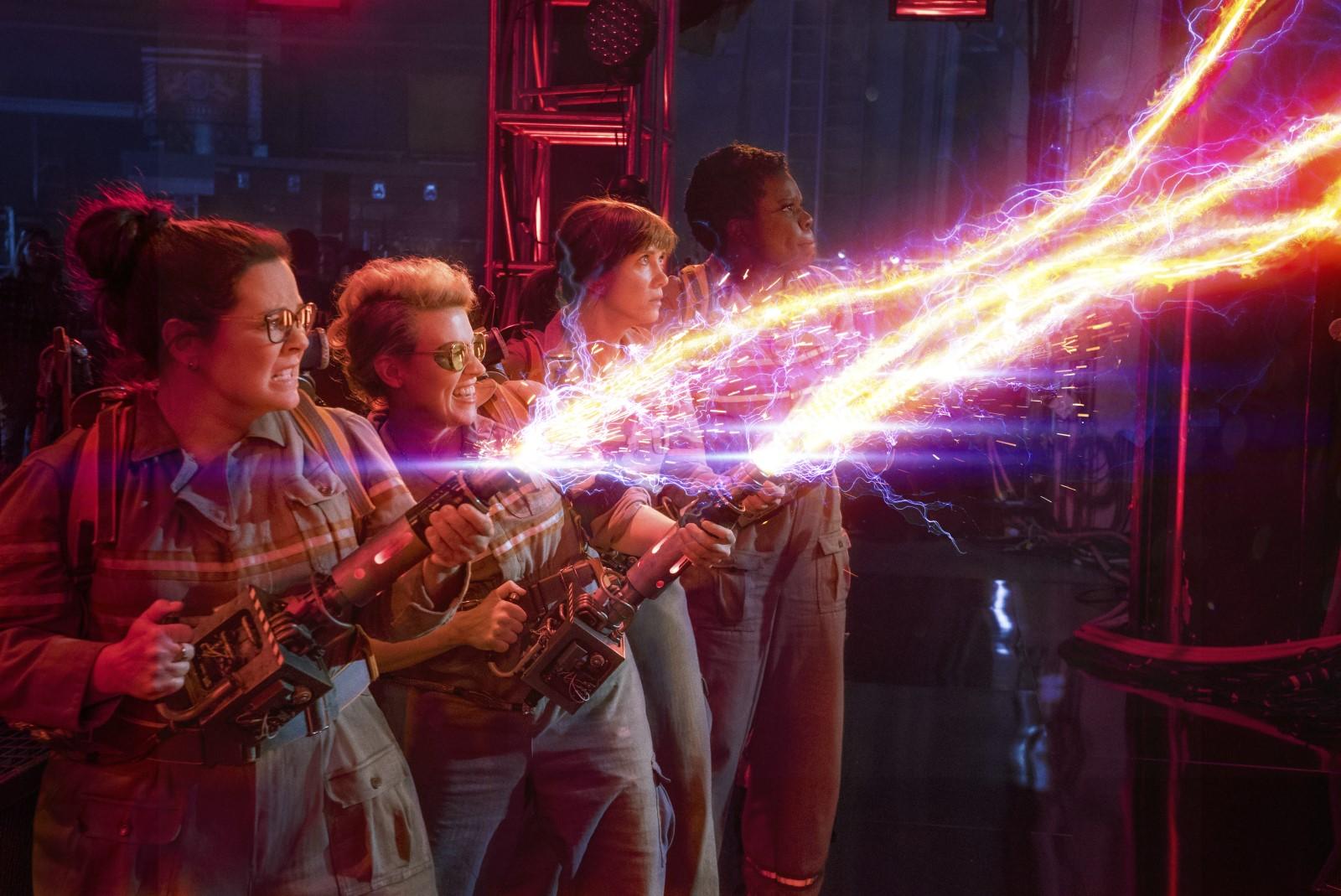 Photo tirée du film S.O.S Fantômes réalisé par Paul Feig. Les quatre actrices sont alignées et lancent des jets face à un fantôme qui semble gigantesque.