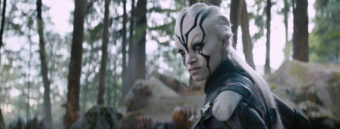 Photo de Sofia Boutella dans le film Star Trek - Sans Limites. L'actrice se retourne et semble prête à combattre un ennemi dans la forêt.