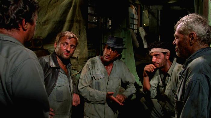 Photo de Bruno Cremer, Roy Scheider et Amidou dans le film Sorcerer de William Friedkin. Les trois acteurs discutent avec deux autres protagonistes dans un bidonville du contrat qu'ils s'apprêtent à accomplir. Leurs vêtements et leur peau sont sales.