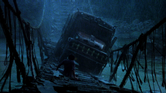 Photo tirée du film Sorcerer de William Friedkin. Le camion traverse un pont secoué par le vent et la pluie. Il est guidé par Amidou que l'on voit de dos, couché sur le pont.