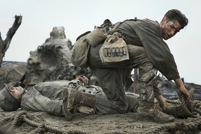 Photo d'Andrew Garfield dans le film Tu ne tueras point réalisé par Mel Gibson, accroupi sur le champ de bataille.