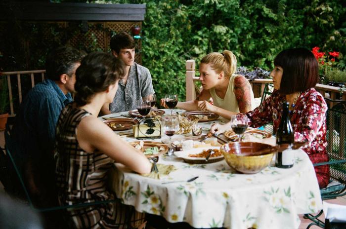 Photo du casting de Juste la fin du monde de Xavier Dolan sur laquelle toute la famille est regroupée sur une table à l'extérieur.