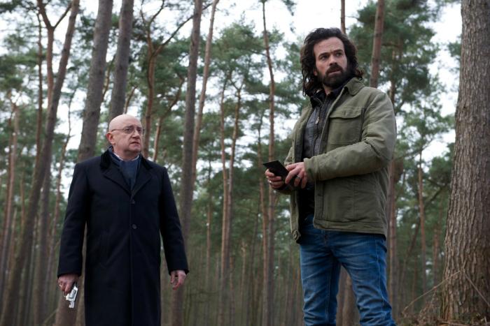 Photo tirée du film Un Petit Boulot sur laquelle Michel Blanc et Romain Duris se tiennent debout, armées dans un bois.