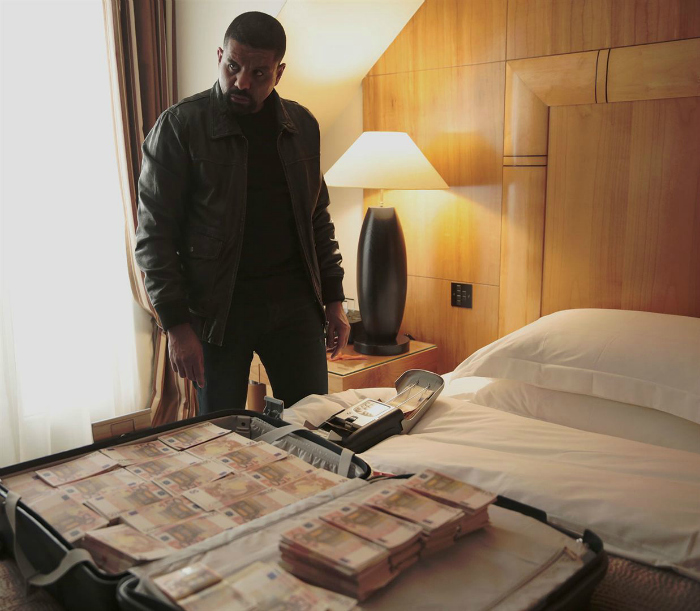 Photo de Youssef Hajdi dans le film Braqueurs de Julien Leclercq. l'acteur est dans un chambre, devant un lit sur lequel est posée une valise de billets.