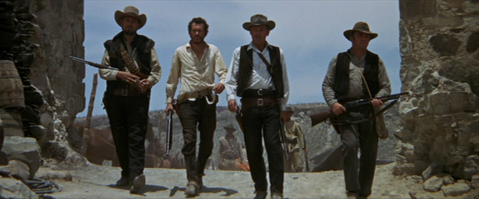 Photo de Ben Johnson, Warren Oates, William Holden et Ernest Borgnine marchant côte-à-côte dans le film La Horde Sauvage de Sam Peckinpah.