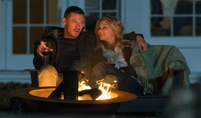 Photo de Luke Evans et Haley Bennett buvant un verre de vin au coin du feu dans le film La fille du train de Tate Taylor.