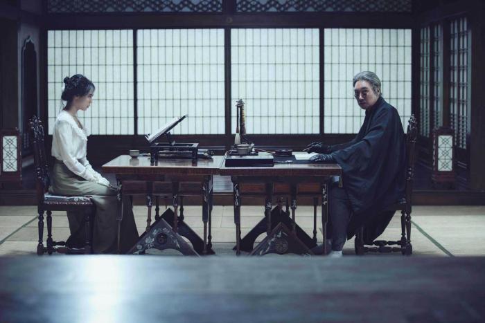 Photo de Kim Min-hee face à Jin-woong Cho assis face à face dans Mademoiselle de Park Chan-wook. Elle s'apprête à lire alors qu'il regarde vers l'objectif avec un air sombre.