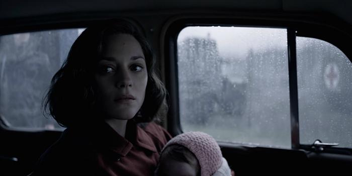 Photo de Marion Cotillard qui tient son bébé et paraît inquiète dans une voiture dans le film Alliés de Robert Zemeckis.
