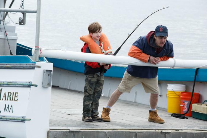 Photo de Casey Affleck dans le film Manchester by the Sea de Kenneth Lonergan. Le personnage fait de la pêche avec son neveu qui tient la canne. Les deux ont l'air passionnés.