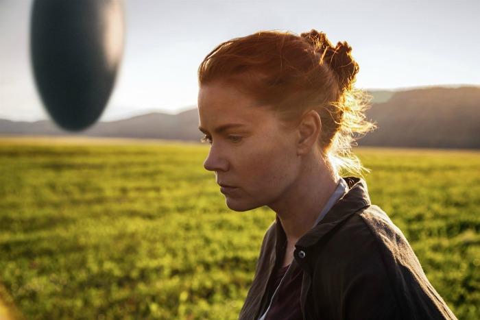 Photo d'Amy Adams qui avance dans l'herbe dans le film Premier Contact de Denis Villeneuve. Le vaisseau extraterrestre est visible au loin.