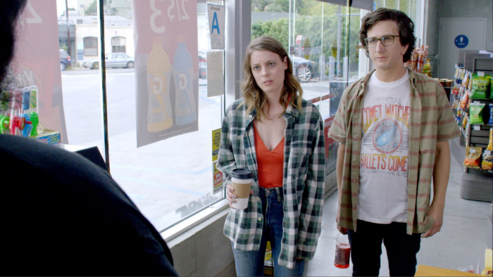 Photo de Gillian Jacobs et Paul Rust en train de fixer la caissier de l'épicerie dans la série Netflix Love.