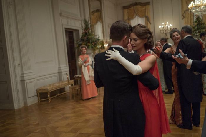 Photo de Nathalie Portman dans le film Jackie de Pablo Larrain. On peut voir Jackie de face danser lors d'un bal avec son mari John Fitzgerald Kennedy, que l'on reconnaît de dos.