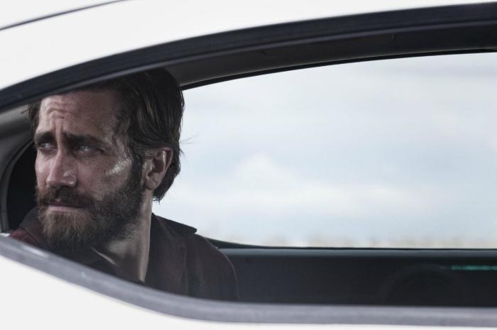 Photo de Jake Gyllenhaal, le visage suintant et poussiéreux à l'arrière d'une voiture dans le film Nocturnal Animals de Tom Ford.