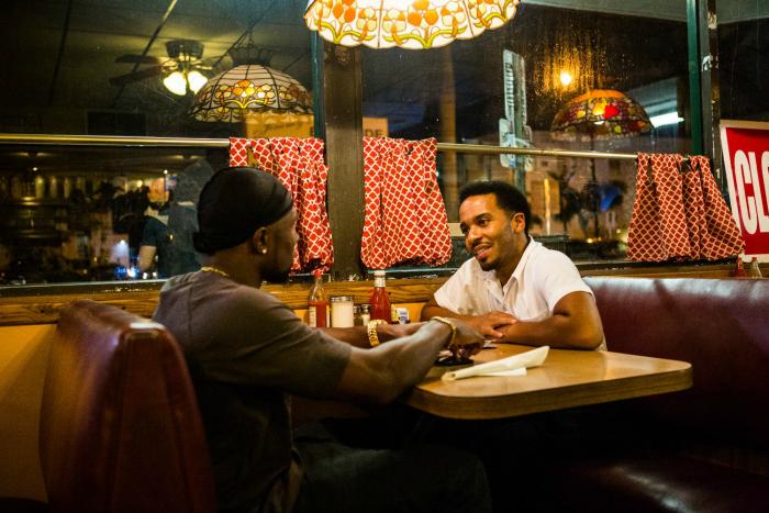 Photo de Trevante Rhodes et André Holland discutant ensemble au restaurant dans le film Moonlight de Barry Jenkins.