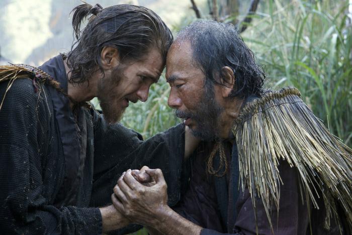 Photo d'Andrew Garfield tenant la main de Shinya Tsukamoto dans le film Silence de Martin Scorsese.