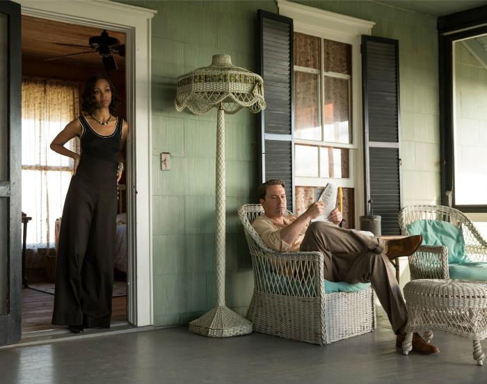 Photo de Zoé Saldana se tenant debout et Ben Affleck assis sur la terrasse d'une maison de Floride des années 20 dans le film Live By Night de Ben Affleck.
