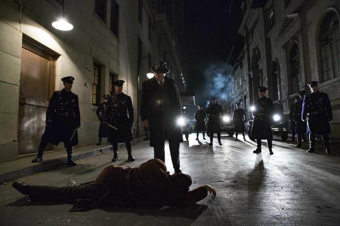 Photo de Ben Affleck blessé à terre aux pieds de Brendan Gleeson et plusieurs autres policiers dans le film Live By Night de Ben Affleck.