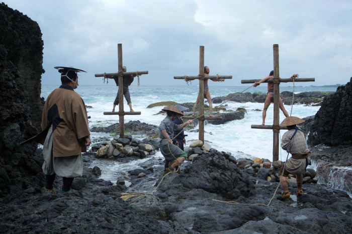 Photo du film Silence de Martin Scorsese sur laquelle des Japonais sont accrochés à des croix devant la mer.
