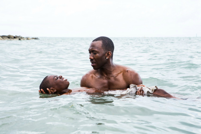 Photo de Mahershala Ali portant Alex R. Hibbert dans l'eau dans le film Moonlight de Barry Jenkins.