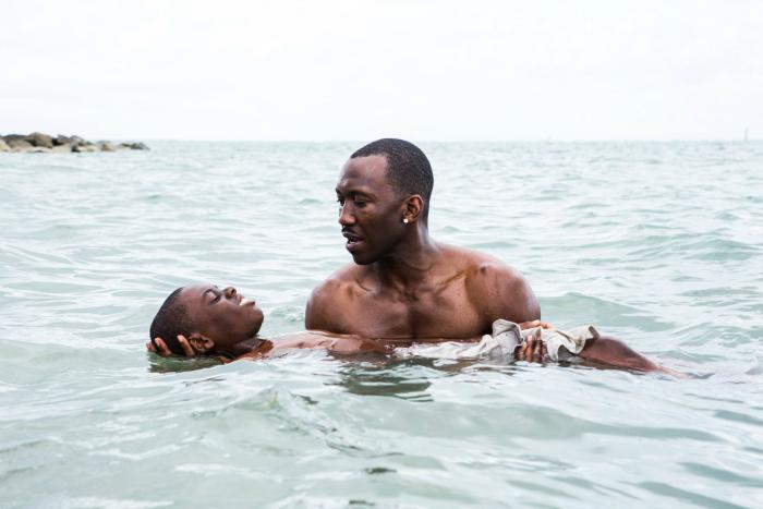 Photo de Mahershala Ali portant Alex R. Hibbert dans l'eau dans le film Moonlight de Barry Jenkins.