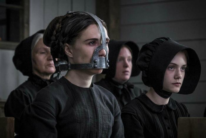 Photo de Carice Van Houten dans le film Brimstone de Martin Koolhoven. Son personnage écoute un discours de son mari à l'église, un prêcheur qui l'a forcé de faire voeu de silence et la force à porter un masque qui l'empêche de parler.