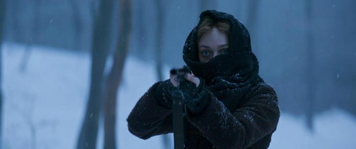 Photo de Dakota Fanning dans le film Brimstone de Martin Koolhoven, qui brandit un fusil dans une forêt enneigée. On ne distingue que ses yeux car elle a le visage couvert par une écharpe.