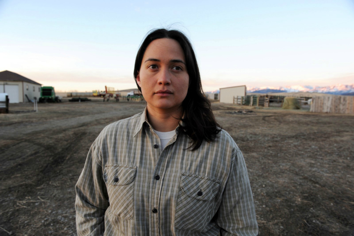 Photo de Lily Gladstone prise face à l'objectif dans son ranch, regardant au loin, dans le film Certaines Femmes de Kelly Reichardt. Les montagnes du Montana sont visibles au loin.