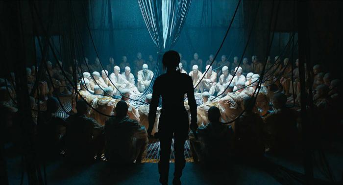 """Photo de Scarlett Johansson dans le film Ghost in the Shell de Rupert Sanders sur laquelle l'actrice est de dos, face à des hommes """"piratés"""" par un cybercriminel."""