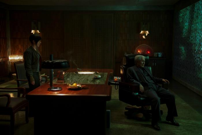 Photo de Scarlett Johansson dans Ghost in the Shell de Rupert Sanders qui se tient debout devant le bureau de Takeshi Kitano. Ce dernier, assis, lui tourne le dos.