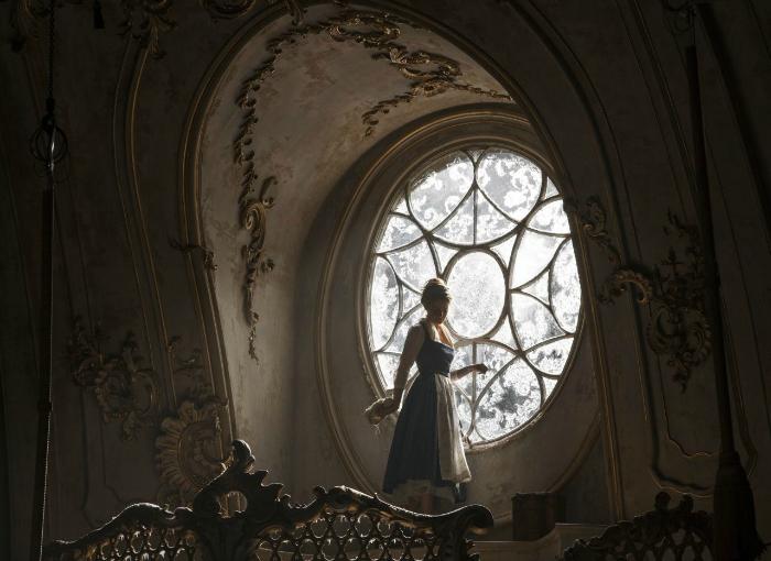 Photo d'Emma Watson dans le film La Belle et la Bête de Bill Condon sur laquelle l'héroïne visite l'aile ouest du château, pourtant interdite. Belle se trouve près d'une fenêtre imposante.