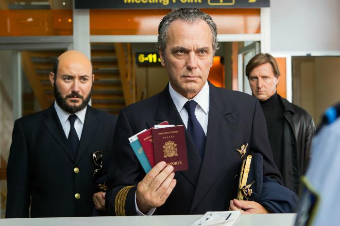 Photo de José Coronado et Carlos Santos dans le film L'homme aux mille visages d'Alberto Rodriguez. Coronado présente deux passeports aux autorités d'un aéroport et Santos se tient juste derrière lui, à sa droite.